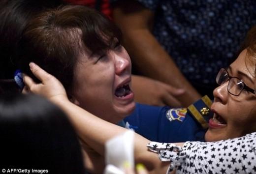 Người thân của những hành khách trên chuyến bay QZ8501 khóc ngất khi nghe tin dữ. Ảnh: AFP