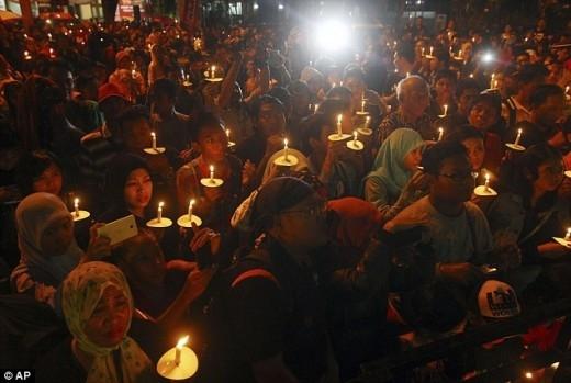 Người dân Indonesia thắp nến cầu nguyện cho các nạn nhân trên chuyến bay QZ8501 vào đêm 31/12. Không khí ngày đầu năm mới của Indonesia trở nên ảm đạm vì thảm kịch bất ngờ này. Ảnh: AP