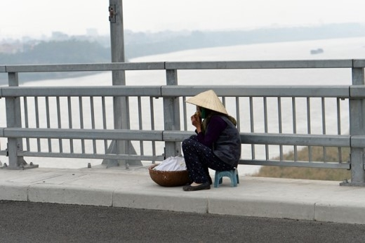 Bà cụ già với thúng hàng ngồi bên thành cầu.