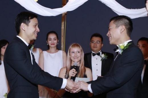 Hai người đàn ông nắm chặt tay nhau khi nghe người chủ hôn (giữa) phát biểu. Ảnh: A.D.