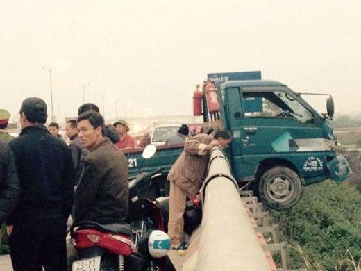 Chiếc xe tải treo lơ lửng trên cầu Thanh Trì sau khi va chạm với xe máy đi cùng chiều khiến người này bị hất văng xuống đường dân sinh.