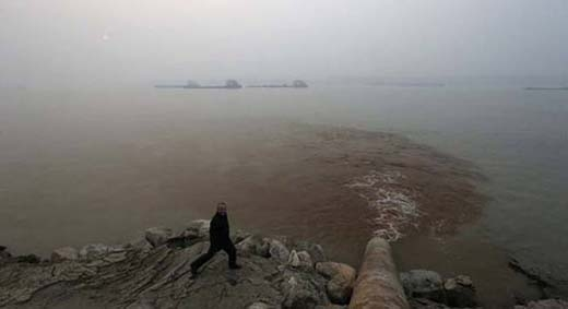 Một người đàn ông tươi cười trước một dòng chảy ô nhiễm từ một nhà máy đổ ra sông.