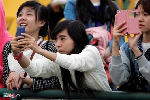 Một fan nữ cố nhoài người qua hàng rào sắt để chụp hình các cầu thủ HAGL.