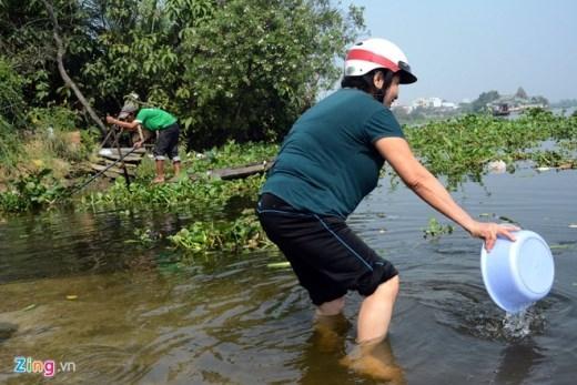 Chứng kiến cảnh này nhiều người phóng sinh lội ra sông, dùng tay, xô, chậu để khua cá ra xa bờ, tránh bị bắt lại.
