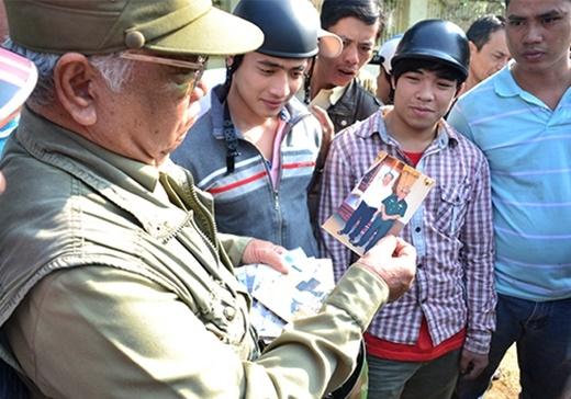 Ông Nguyễn Hữu Tài cho mọi người xem những bức ảnh chụp cùng ông Nguyễn Bá Thanh. Ảnh: Nguyễn Đông.