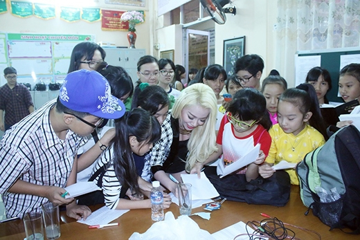 Sau khi kết thúc màn trình diễn, nữ ca sĩ được các em học sinh vây kín xin chữ kí.