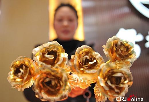 Một cửa hàng ở tỉnh Chiết Giang, Trung Quốc, bày bán những bông hồng bằng vàng ròng 24 caras, nhân ngày 14/2. Nhiều khách hàng tỏ ra thích thú với bông hồng tình yêu đặc biệt này. Ảnh: CRI