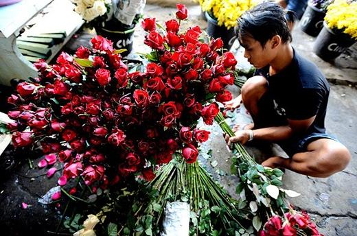 Người bán hoa bận rộn chuẩn bị hoa hồng để phục vụ các cặp đôi tới mua tại khu chợ truyền thống ở Surabaya, Indonesia. Ảnh: Getty