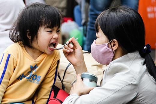 Chị Lành quê huyện Nghĩa Hành, Quảng Ngãi vẫn chưa mua được vé về quê. Chị phải cho bé ăn tại chỗ trong khi canh hành lý để chồng xếp hàng mua vé.