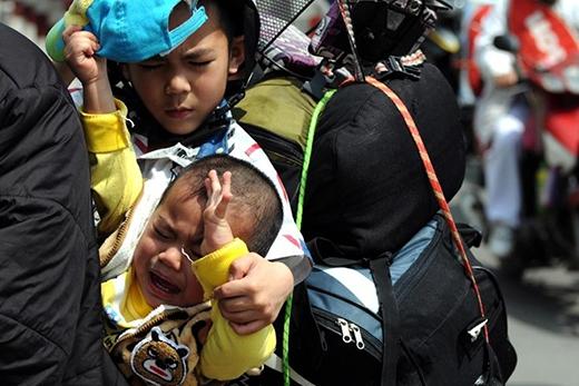 Cậu bé cố gắng dỗ dành em trai đang khóc thét vì mệt và đói khi cha lái xe vượt qua khu tắc đường.