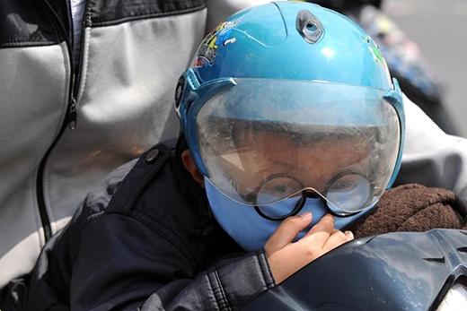 Bé Minh dù đã trang bị khẩu trang và kính chống khói bụi nhưng cũng không khỏi mệt nhoài vì ngột ngạt.