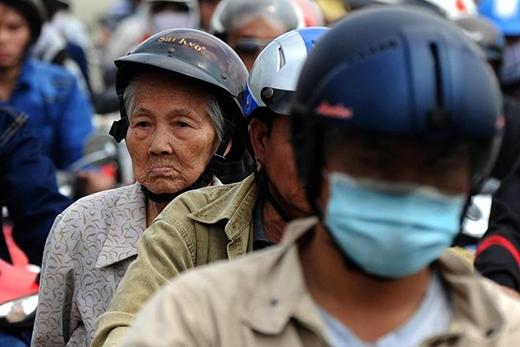 Một cụ già ngồi chịu trận khi kẹt trong đám đông xe cộ.