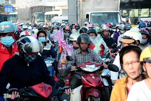 Một số người đi đường chật vật ôm đồ đac, quà tết giữa dòng người đông đúc.