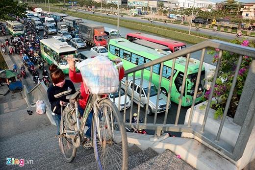 Hai nữ công nhân bê xe đạp lên cầu vượt để qua đường.