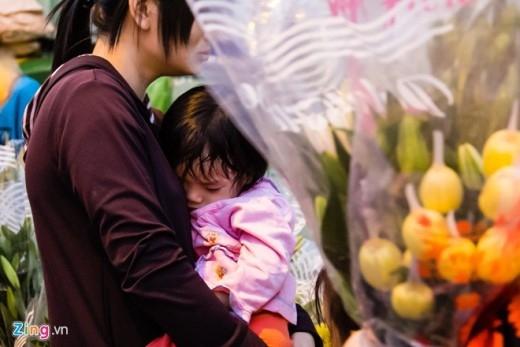 Một em nhỏ đi theo mẹ ra chợ hoa và ngủ thiếp đi.