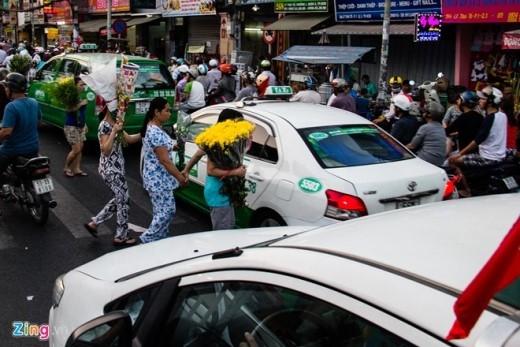 Từng đoàn người mua hoa đi bộ luồn lách giữa xe máy, ô tô.