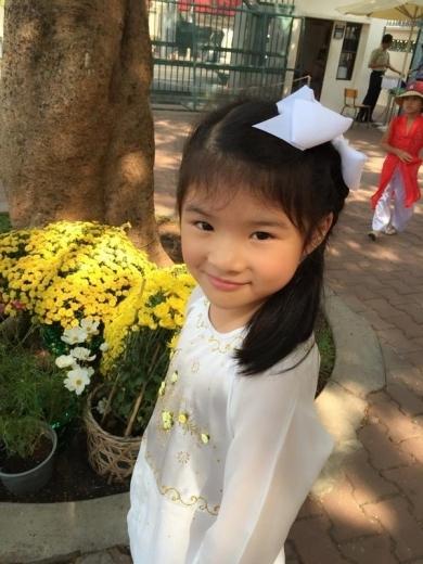 Con gái Trương Ngọc Ánh e thẹn trong tà áo dài. Kiểu dáng áo với phần cổ cách tân, chất liệu voan mỏng nhẹ cùng phụ kiện ton-sur-ton giúp cho Bảo Tiên trông thật đáng yêu.