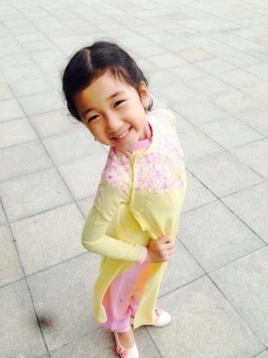 Bé Khánh Linh - con gái của hoa hậu Nguyễn Thị Huyền - thừa hưởng nhiều nét xinh xắn của mẹ. Cô bé tạo dáng nhí nhảnh và vui tươi khi diện áo dài màu vàng thêu hoa màu hồng.