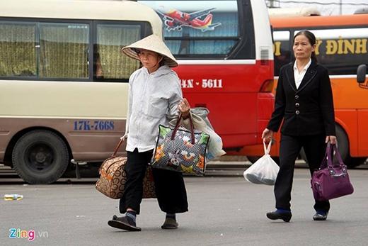 Bà Tiến quê từ Lào Cai xuống Hà Nội với các con cho biết, xe đến bến xe Mỹ Đình chỉ muộn hơn mọi khi khoảng 15 - 20 phút và giá vé vẫn giữ nguyên như trước Tết. Ảnh: Mạnh Thắng.
