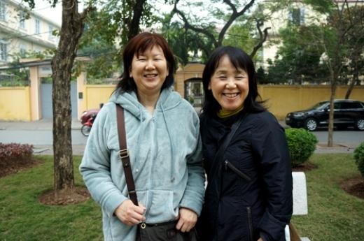 Hai người phụ nữ tỏ ra ngạc nhiên và òa lên thích thú khi nhìn thấy những người bán hoa đào trên phố.
