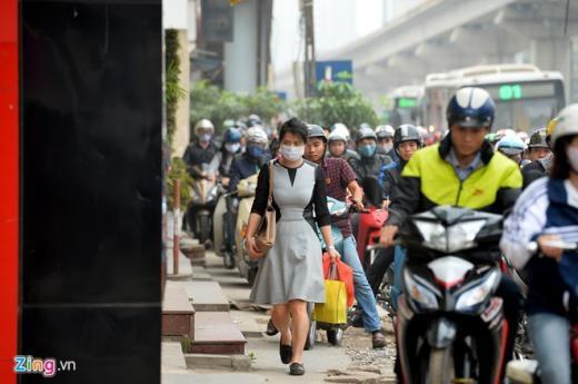 Một phụ nữ ngồi sau xe máy phải bước xuống đi bộ tiến lên phía trước để người chở mình di chuyển dễ dàng hơn trên vỉa hè lổn nhổn gạch đá.