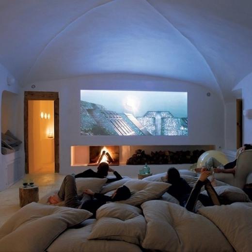 Một phòng lớn có lò sưởi và màn hình máy chiếu 50 inch.