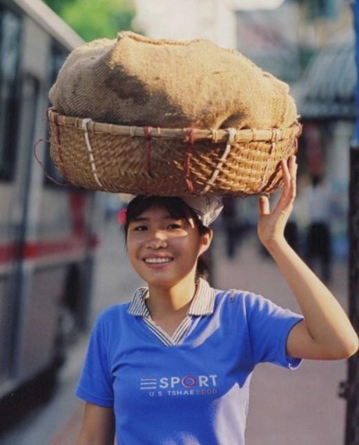 Hiền đội thúng bán bánh mì tại khu vực bờ hồ Hoàn Kiếm. Hiền cho biết việc bán hàng tại đây ngoài việc giúp đỡ gia đình còn giúp cô bé nâng cao trình độ tiếng Anh.
