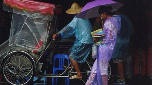 Tại cửa đền Bà Kiệu, một cô bé đi bán áo mưa cho khách du lịch.