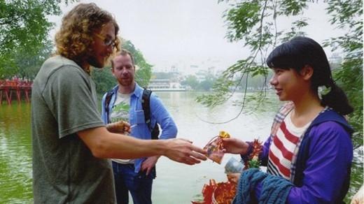 Em Chi (hiện theo học lớp 12) đi bán túi cầu may cho khách du lịch nước ngoài tại bờ hồ Hoàn Kiếm sáng mùng 1 Tết Ất Mùi.