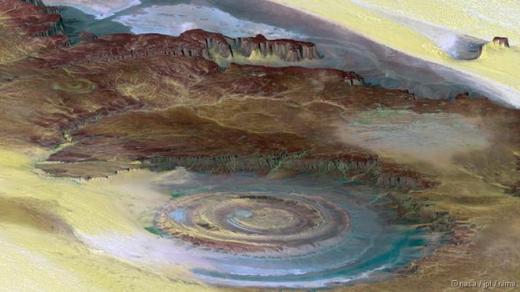 Con mắt Sahara, còn được gọi là cấu trúc Richat, hình thành trên sa mạc Sahara. Đây là một khối đá có hình vòm rộng khoảng 50 km. Nhiều người từng cho rằng nó xuất hiện sau tác động của một vụ va chạm thiên thạch. Ngày nay, nó được cho là hình thành từ những tảng đá trồi lên mặt đất nhưng sau đó xói mòn. Ảnh: NASA