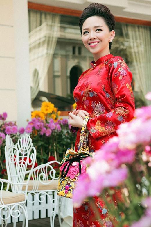 Chiếc túi gấm vàng vừa nổi bật vừa hòa hợp với màu đỏ nổi bật của tà áo dài.