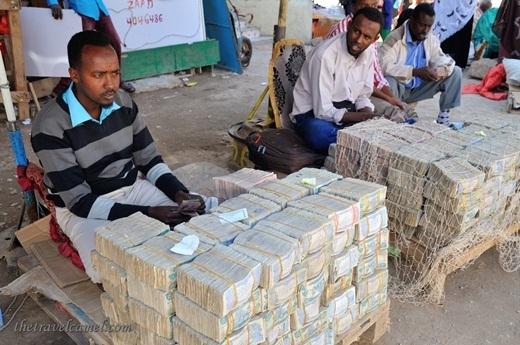 Dọc đường phố Somalia, dễ dàng bắt gặp các thương nhân ngồi trên vỉa hè nhấm nháp trà với phía trước chất đầy vàng bạc và các bọc tiền được chất thành đống.