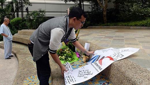 Một thanh niên đặt tấm biểu ngữ ghi những lời chúc tốt lành gửi đến ông Lý.