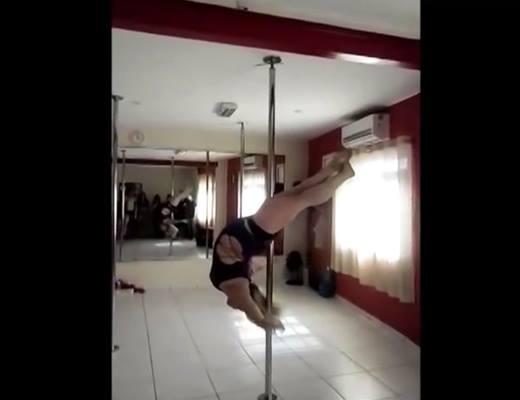 Cô gái đu thân mình trên cây cột.