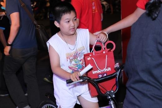 Một em bé cực kì thích thú khi nhận được phần ăn miễn phí sau khi tự xếp hàng bằng chiếc xe đạp nhỏ của mình
