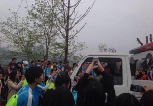 Đám đông vẫn chưa tản đi kể cả khi anh đã trốn vào trong xe