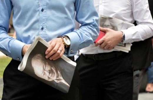 Trên tay mỗi nhân viên văn phòng là một tờ báo có chân dung ông Lý.