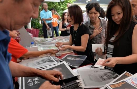 Nhân viên tại các quầy bán báo luôn tay để lấy báo cho khách. Họ mặc áo đen để bày tỏ sự kính trọng với cố thủ tướng.