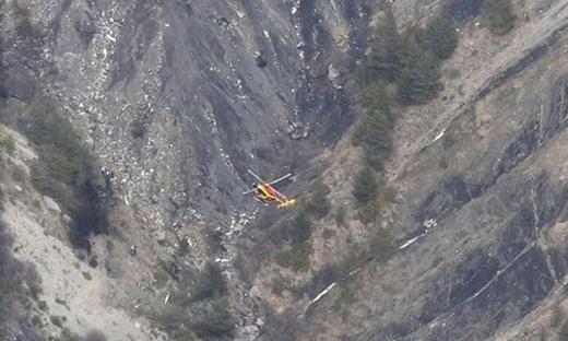 Một trong những bức ảnh đầu tiên về hiện trường cho thấy một trực thăng lượn vòng bên trên sườn núi với nhiều mảnh vỡ nhỏ.