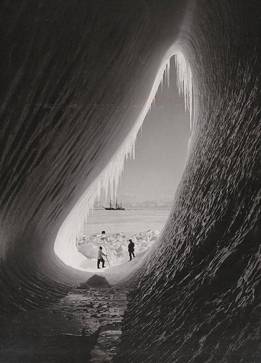 Hai người đàn ông đứng trước một hang động băng trong cuộc thám hiểm chinh phục nam cực của Anh vào tháng 1 năm 1911.