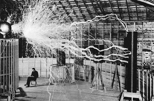 Nikola Tesla trong phòng thí nghiệm của mình với các cuộn dây truyền tải điện hàng triệu volt qua không khí.