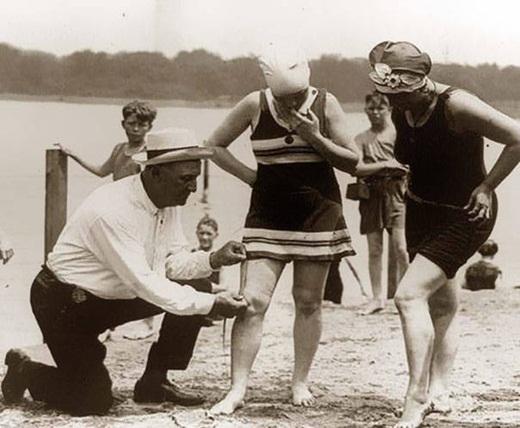 Một người đàn ông đang đo chiều dài bộ đồ bơi của những người phụ nữ để xem đồ bơi của họ có quá ngắn so với mức quy định hay không vào những năm 1920.