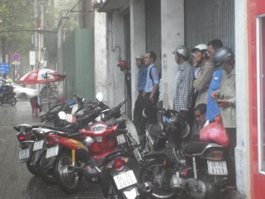 Nhiều người đi đường không đem theo áo mưa, trở tay không kịp và phải đứng trú mưa ở dưới mái hiên nhà