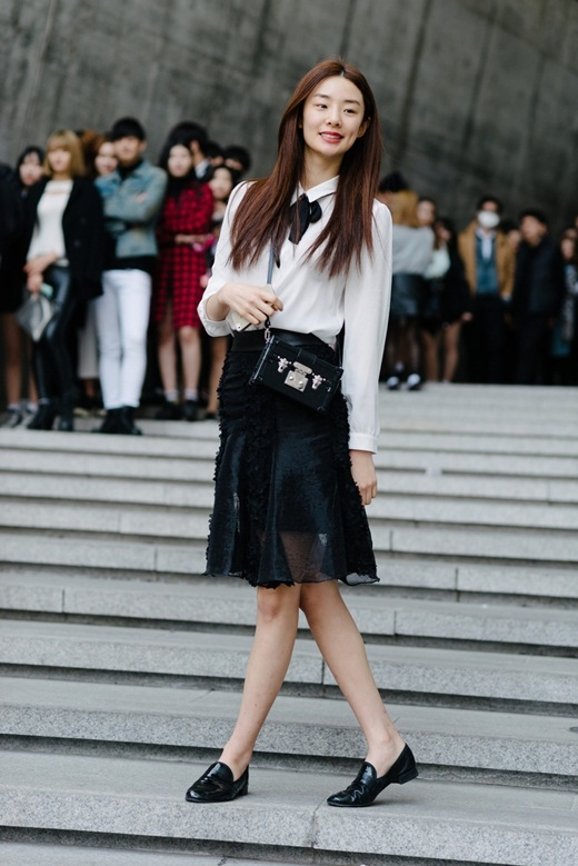Cô gái này thì chọn cho mình phong cách nhẹ nhàng nữ tính cùng áo sơ mi trắng cơ bản đi kèm với chân váy sheer màu đen.