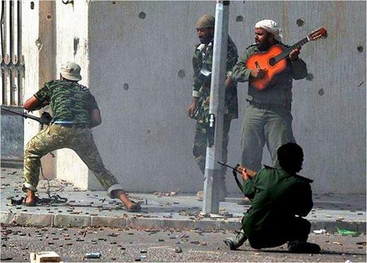 Một người đàn ông vẫn bình tĩnh và vô từ chơi đàn giữa làn súng đạn nguy hiểm