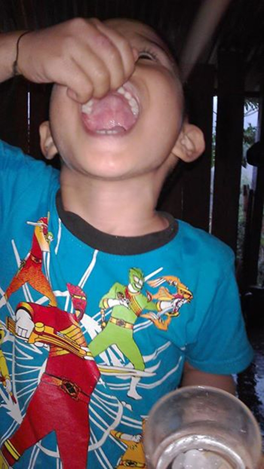 Một đứa trẻ ở Mai Sơn nhặt đá cho vào miệng ăn mong muốn sẽ gặp nhiều may mắn (Ảnh: Bùi Thị Lan).