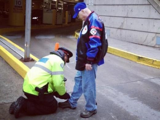 Cụ già này đang được một cảnh sát cột lại dây giày cho mình. Một chút quan tâm thế này là đủ để vui cả ngày rồi!