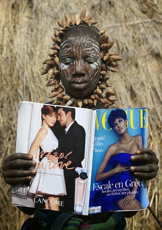 Một người phụ nữ thuộc bộ lạc Mursi lần đầu đọc tạp chí Vogue.