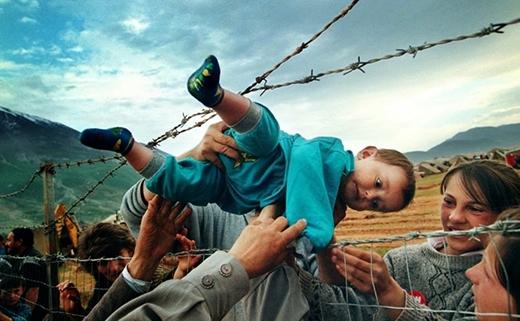 Một đứa trẻ được đưa qua hàng dây thép gai cùng ông bà của mình tại một trại tị nạn trong cuộc chiến Kosovo.