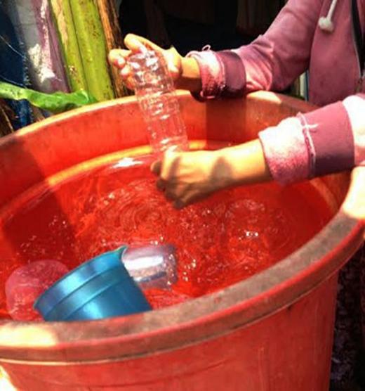 Các bình nhựa chứa nước được súc rửa trong một cái thùng lớn.